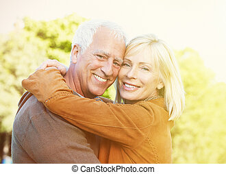 Old people over park background - Two aged smiling people...
