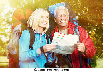 Old people with rucksacks - Two aged smiling people with...