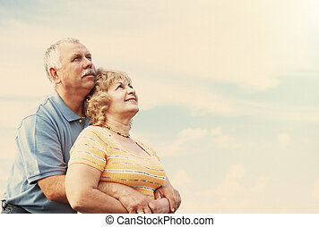 Old people over sky background - Two aged smiling people...