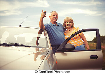 Two elderly people nesr car with keys - Two happy smiling...