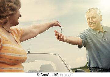 Two elderly people nesr car with keys