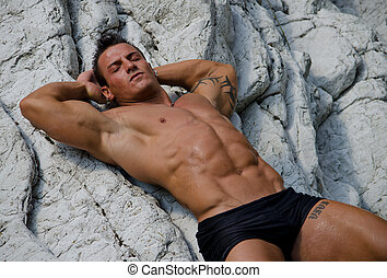 Handsome young man laying naked on white rocks, eyes closed...