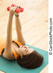 Weight lifting - An Asian lady laying down doing weight...