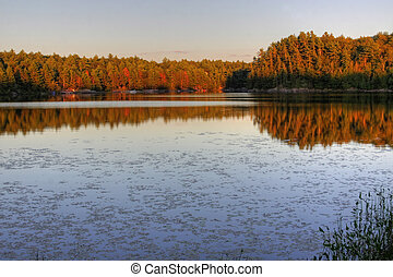 Muskoka Lake at Sunset - A lake in cottage country at...