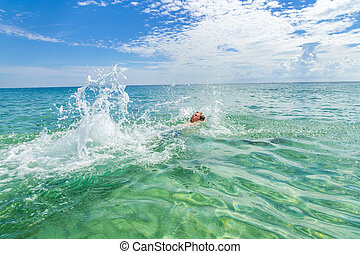 handsome teen backstroking in the ocean - handsome teen...