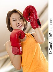 Lady boxer - An Asian lady in boxing pose in a gym.