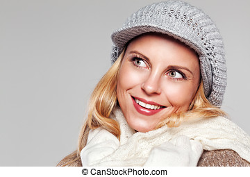 Close up of a blonde woman in fall fashion isolated on grey