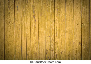 Old fence painted in yellow, wooden background