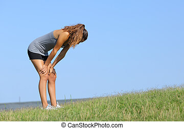 Fitness woman tired resting on the grass with the sky in the...