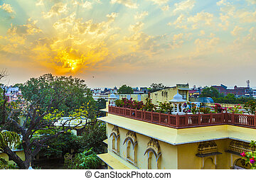 sunset in Jaipur from the roof of the hotel with view over old trees