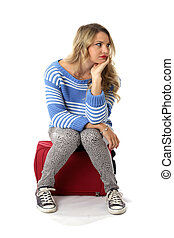 Model Released. Bored Young Woman Sitting on a  Red Suitcase