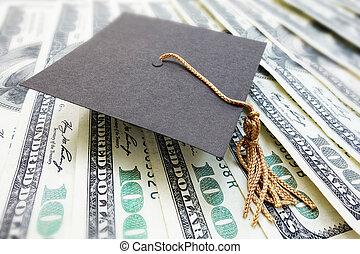 mortar board cash - closeup of a mini graduation cap on cash...