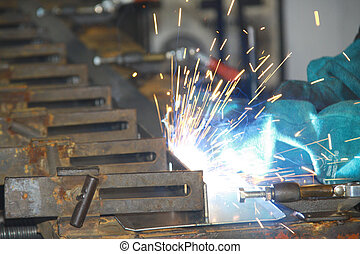 Worker welding pieces on a production line