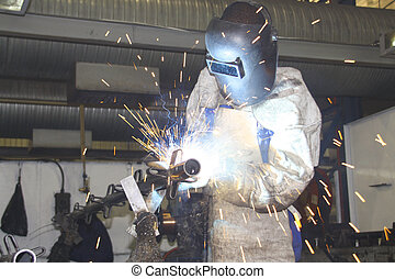 Worksman labourer welding a metal component