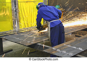 Industrial worker grinding metal sheets - Industrial worker...