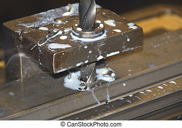 Industrial drill pirecing a piece of steel