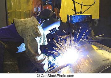 Welding on tank - Labourer welding a custom steel tank