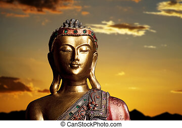 Buddha Statue at Sunset - Golden Buddha statue against a...