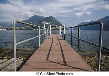 Alpine lake with a pier and mountain and blue sky with...