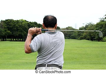 Male golf player teeing off