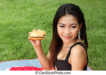 Teenage Girl Eating a Cheeseburger in the park