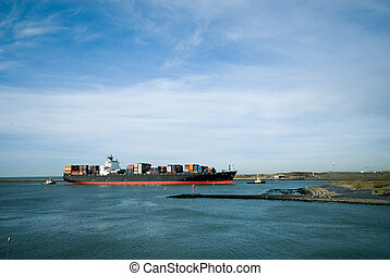 big containership being tugged into the harbor