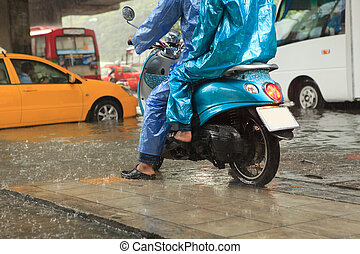 two man wearing raincoat riding motorcycle