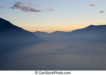 Alpine lake with fog in blue hour and mountain