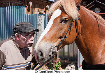a man kisses a horse near a rural house