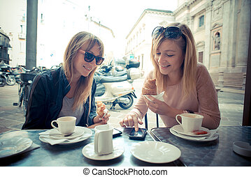two beautiful blonde women talking at the bar in the city
