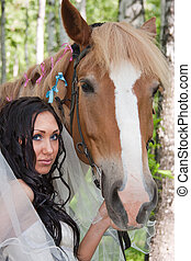 young woman in the dress of fiancee next to a horse