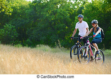 Young Happy Couple Riding Mountain Bikes Outdoor Healthy...