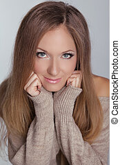 Closeup beauty portrait of young smiling woman with make up and long hair isolated on grey background. Studio Photo