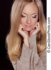 Make up and Hairstyle. Beautiful blond woman with long hair. Closeup portrait of a beauty girl posing at studio isolated on black background.