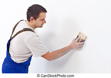 Worker scrubbing the wall with sandpaper - preparing the...