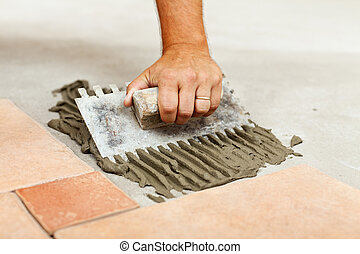 Laying ceramic floor tiles - man hand spreading adhesive...