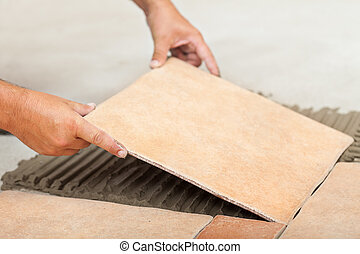 Man lays ceramic floor tiles - closeup - Laying ceramic...