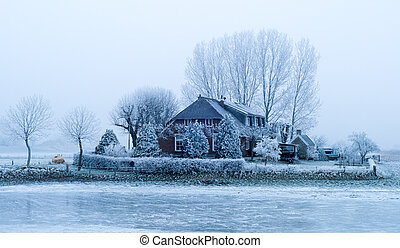 dutch farmhouse with white frozen trees in winter