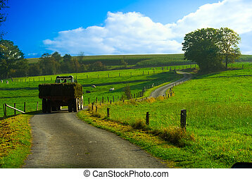 beautiful farmland landscape - tractor with hay in a...