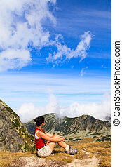 Top of the World - Woman sitting on the top of the moutain...