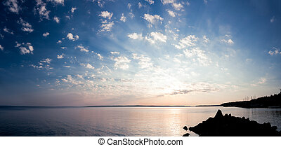 Tranquil sunrise panorama of lake and clouds