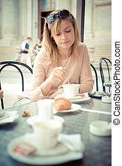 beautiful blonde woman having breakfast at the bar