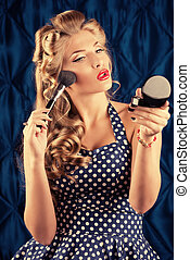 blusher - Portrait of a charming pin-up girl doing makeup in...