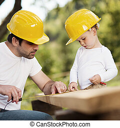 Father and son - Little son helping his father with building...