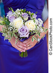 bridesmaid holding a wedding bouquet of white and purple...