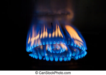 a flame burning on a gas stove in the kitchen