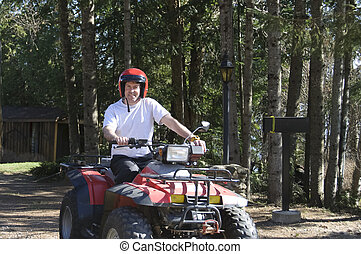 young man riding a Quad in Quebec rural road, Canada