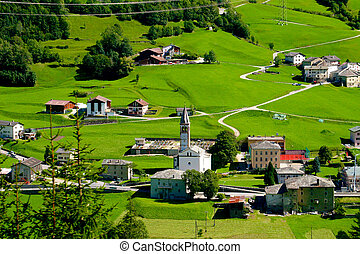 View from Bernina Express, Alpine village with a church in...