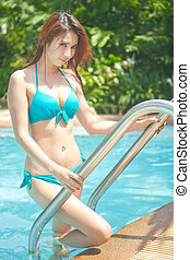 Woman going out of the swimming pool - Pretty young asian...