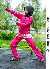 young woman making tai chi exercise